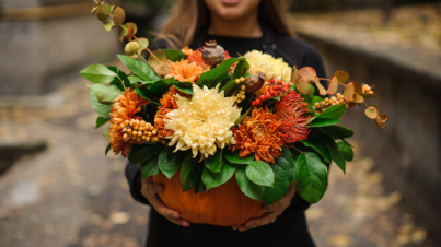 Woman holding a pumpkin with autumn flowers